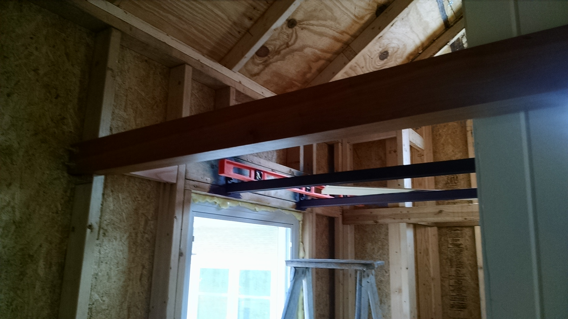 this window is above the kitchen countertop, the steel joists are seen attached above the window, and at the front of the loft is a cherry beam